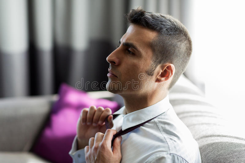 Businessman taking off his tie at hotel room. People concept - businessman taking off his tie at hotel room royalty free stock photography