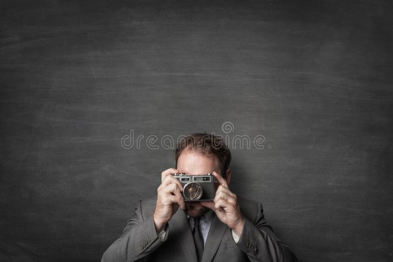 Businessman taking a photo with old vintage camera royalty free stock images