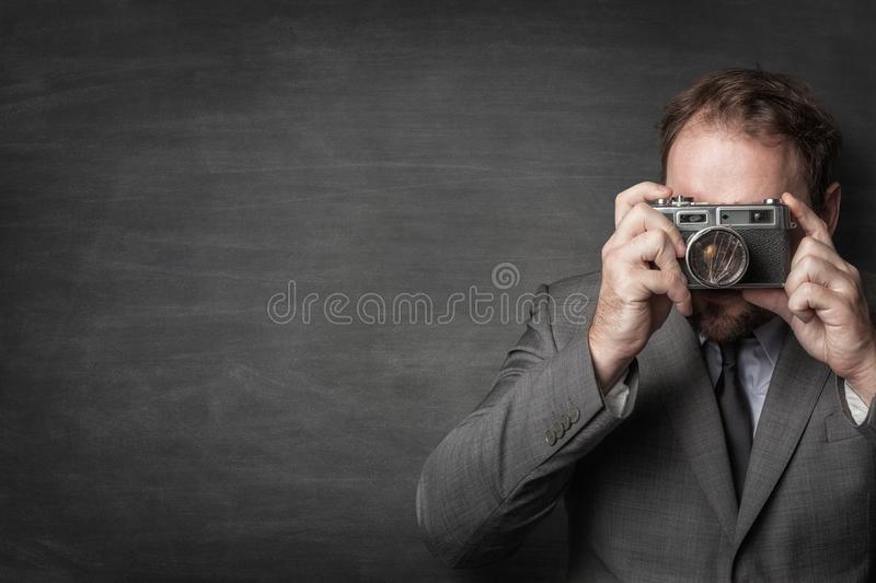 Businessman taking a photo with old vintage camera royalty free stock photo