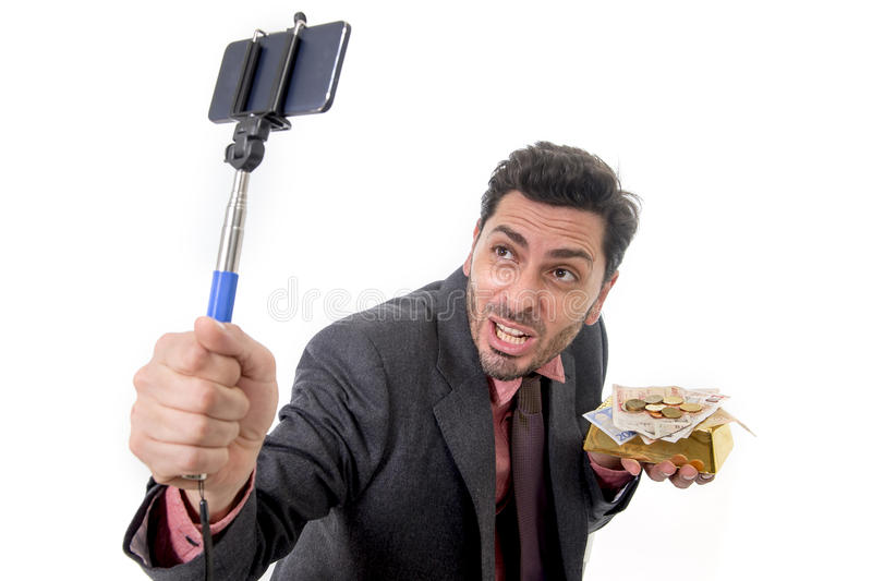 Businessman taking selfie photo with mobile phone camera and stick posing happy and successful with gold bar and money royalty free stock photos