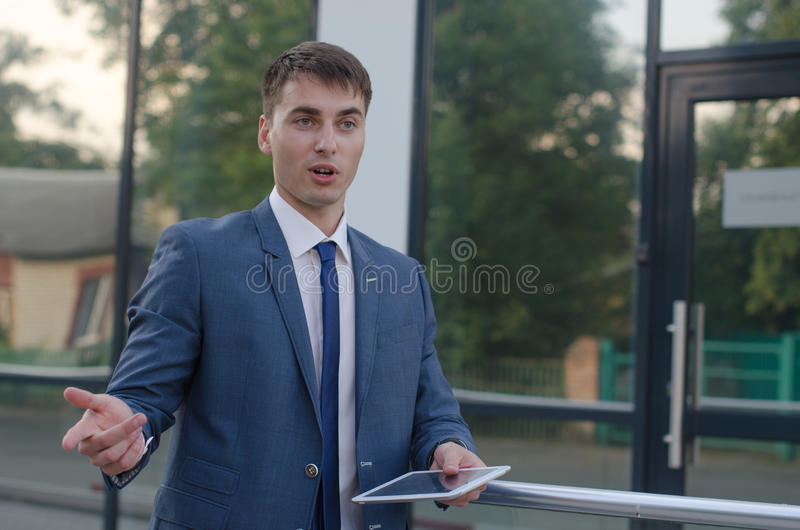 Businessman talk with laptop in left hand stock photo