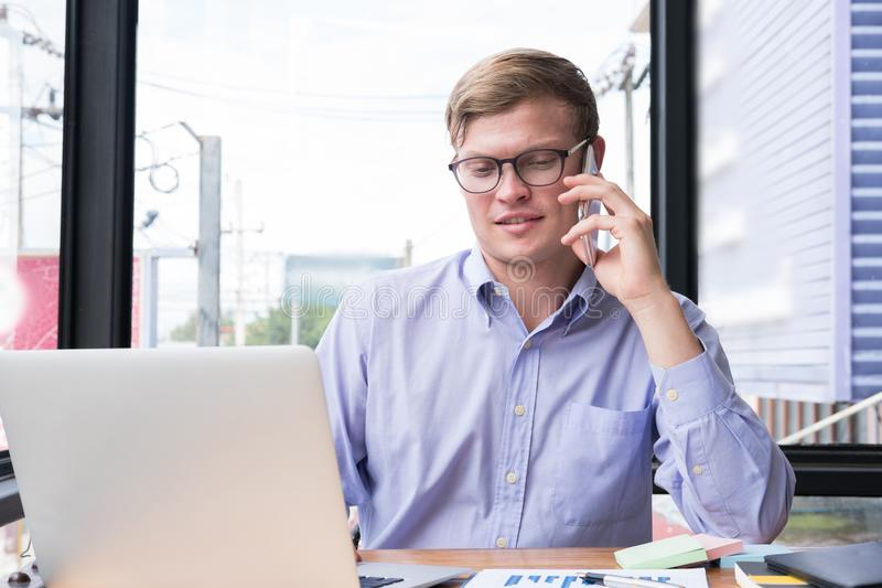 Businessman talk on mobile phone at office. young man call on sm. Art phone at workplace. male employee use cellphone at work. business communication, lifestyle stock photo