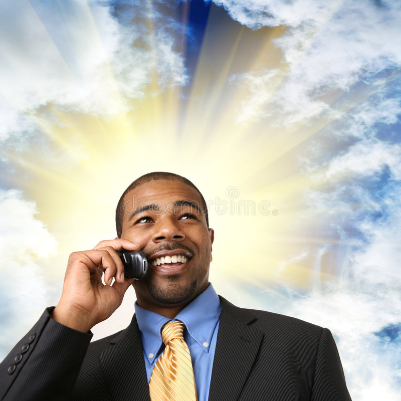 Businessman talking on cell phone. African American businessman talking on mobile phone, smiling stock photo