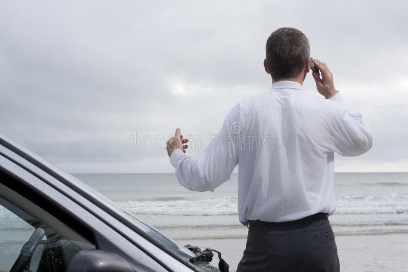 Businessman talking on cell phone at the sea stock photos