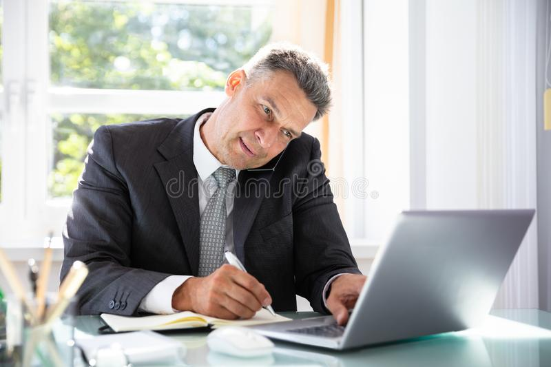Businessman Talking On Cellphone While Writing Schedule In Diary. Businessman Talking On Cellphone And Using Laptop While Writing Schedule In Diary royalty free stock image