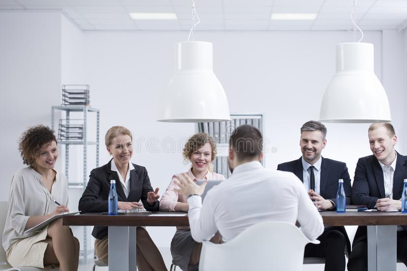 Businessman talking about innovative idea. Businessman talking about an innovative idea to a group of satisfied investors royalty free stock images