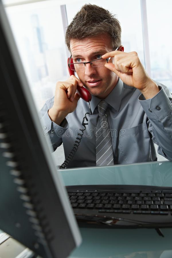 Download Businessman Talking On Landline Phone In Office Stock Photo - Image of concentrating, grey: 13140410