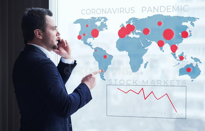 Businessman talking on mobile looking at map of coronavirus pandemic and economy and financial markets collapse by. Businessman talking on smartphone looking at royalty free stock images