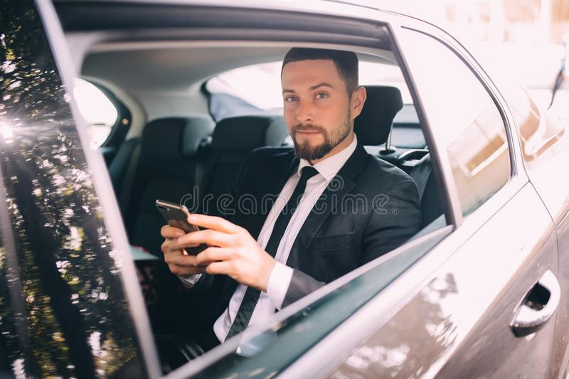 Businessman talking on the mobile phone and looking outside the window while sitting on back seat of car. Male business executive. Businessman talking on the royalty free stock photo