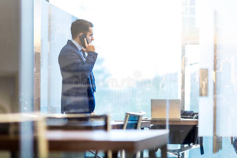 Businessman talking on a mobile phone while looking through window in NY stock images