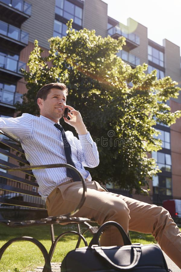 Businessman Talking On Mobile Phone During Lunch Break In Park royalty free stock images