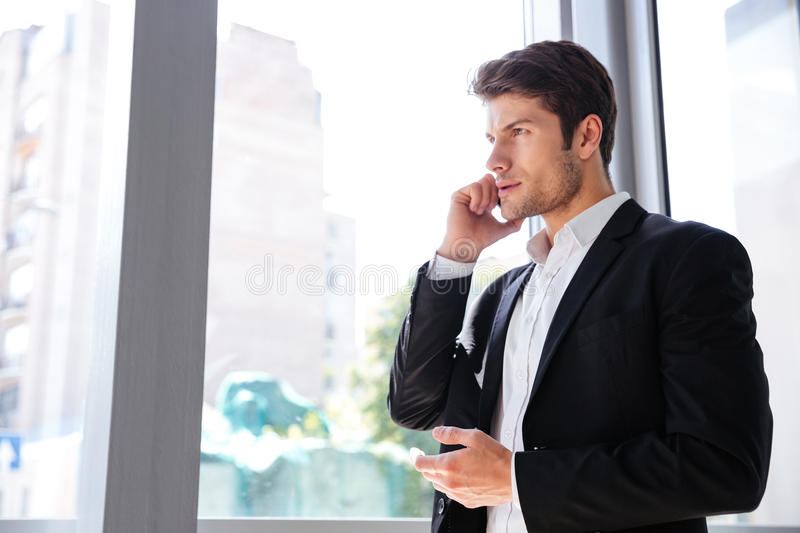 Businessman talking on mobile phone near the window in office royalty free stock photography