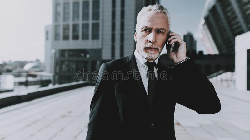 Businessman is Talking on Mobile Phone stock photos