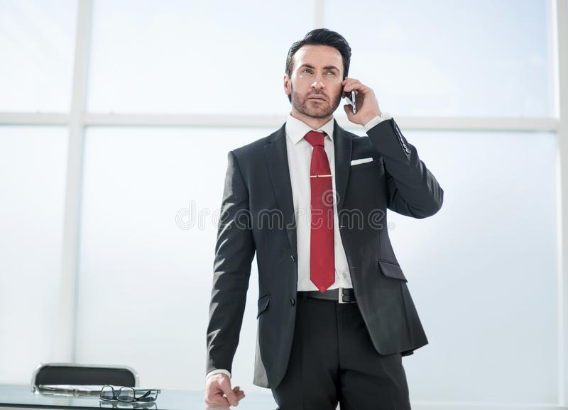Businessman talking on mobile phone standing in the office stock images