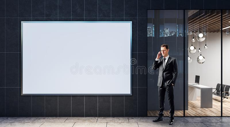 Businessman talking on the phone near blank white banner on a wall of business center royalty free stock photo