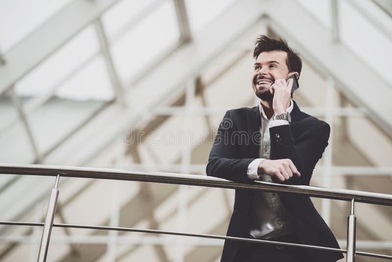 Businessman talking on phone near buildings. stock photo