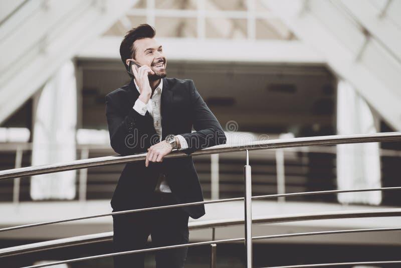 Businessman talking on phone near buildings. stock photos