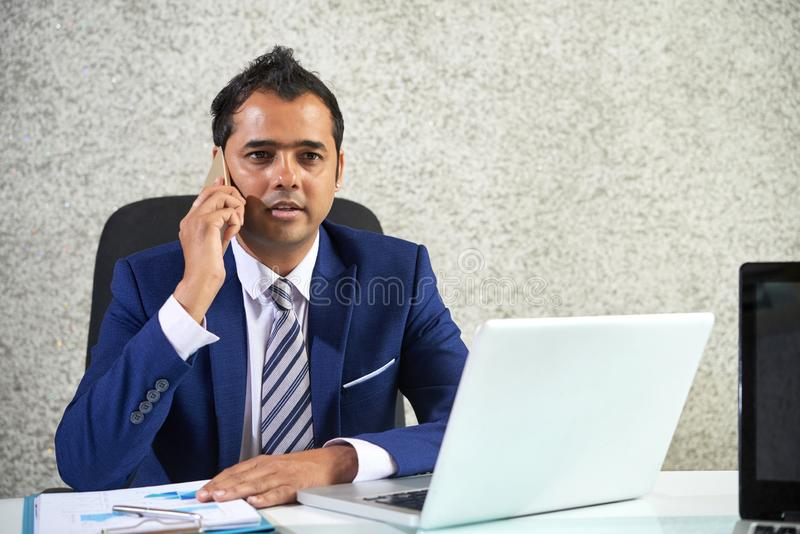 Businessman talking on the phone at office royalty free stock images