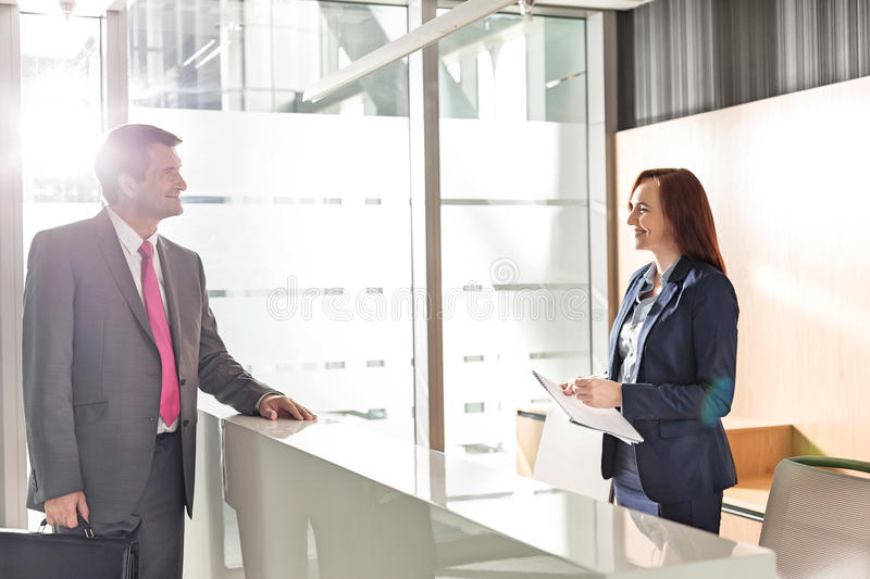 Businessman talking with receptionist in office royalty free stock photos