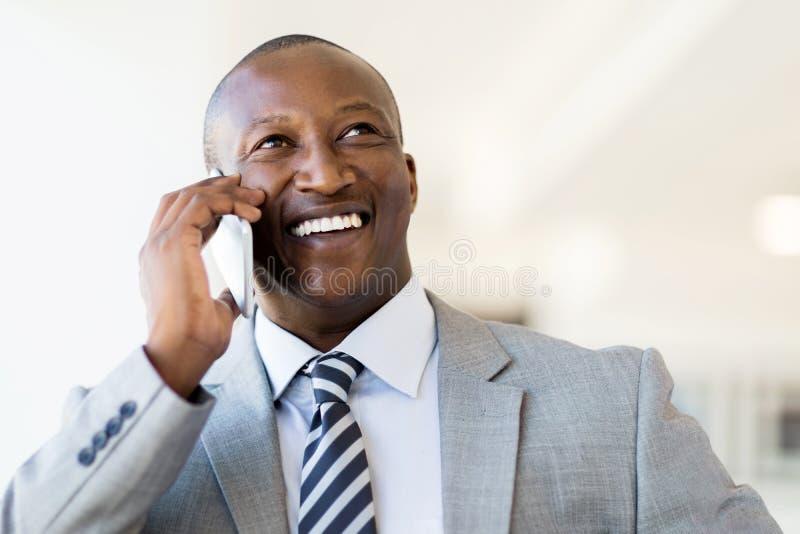 Businessman talking smart phone. Cheerful black businessman talking on smart phone in office royalty free stock image