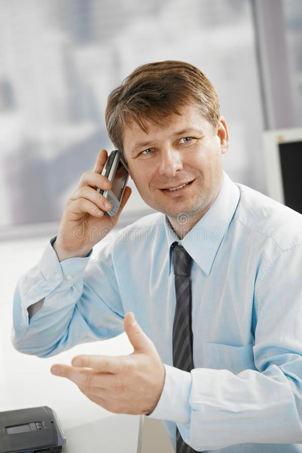 Businessman talking on smartphone royalty free stock photo