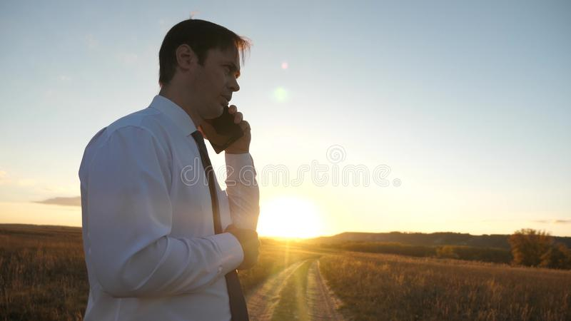 Businessman talking on a smartphone against the sky. man in a tie with a tablet in the park at sunset. talking mobile stock photo