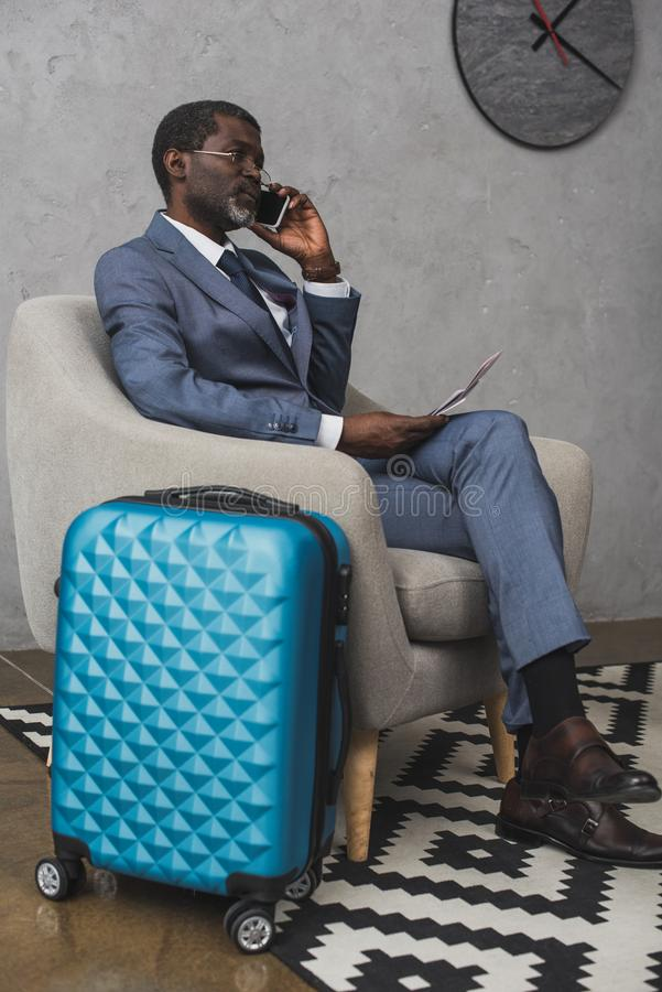 Businessman talking by smartphone and sitting in armchair travel bag. Standing near stock photos