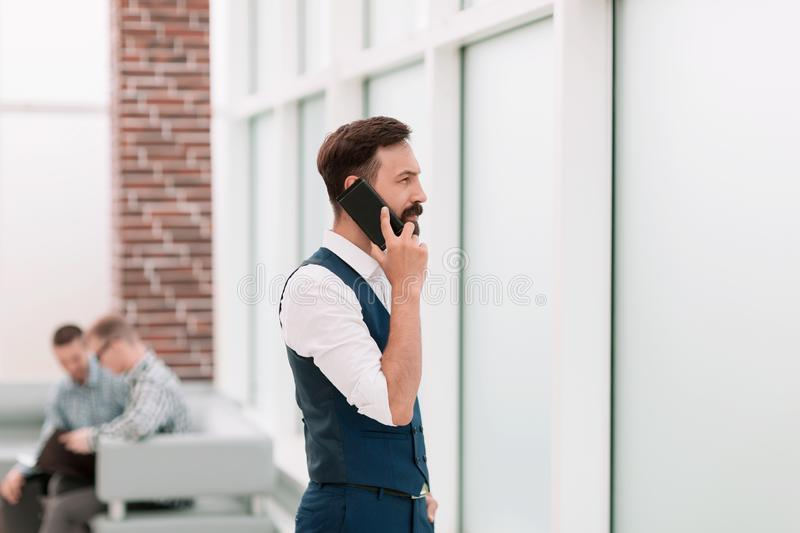 Businessman talking on a smartphone while standing in the office royalty free stock photos