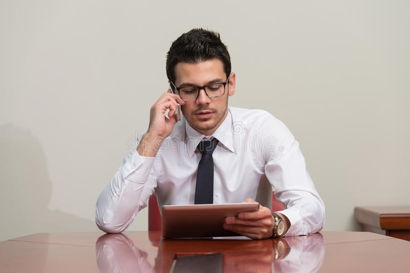 Businessman Talking On Telephone In Office. Young Businessman Working At His Tablet While Talking On The Phone stock photography