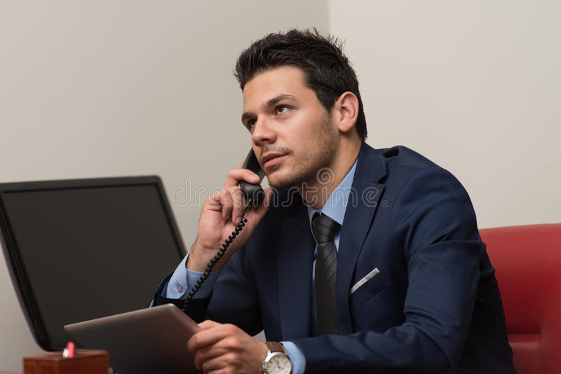 Businessman Talking On Telephone And Using Computer Stock Photo