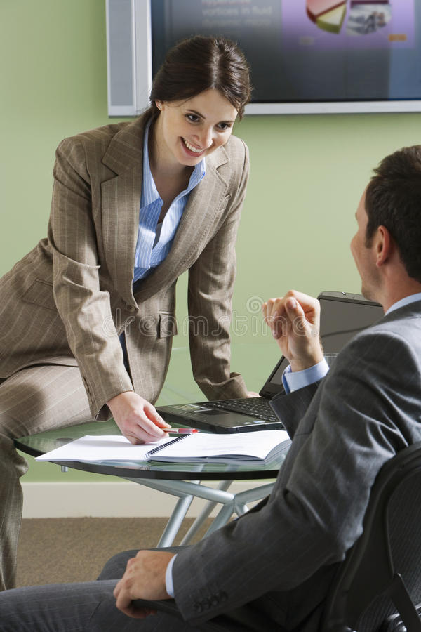 Businessman talking to businesswoman at desk in office, smiling, rear view royalty free stock images