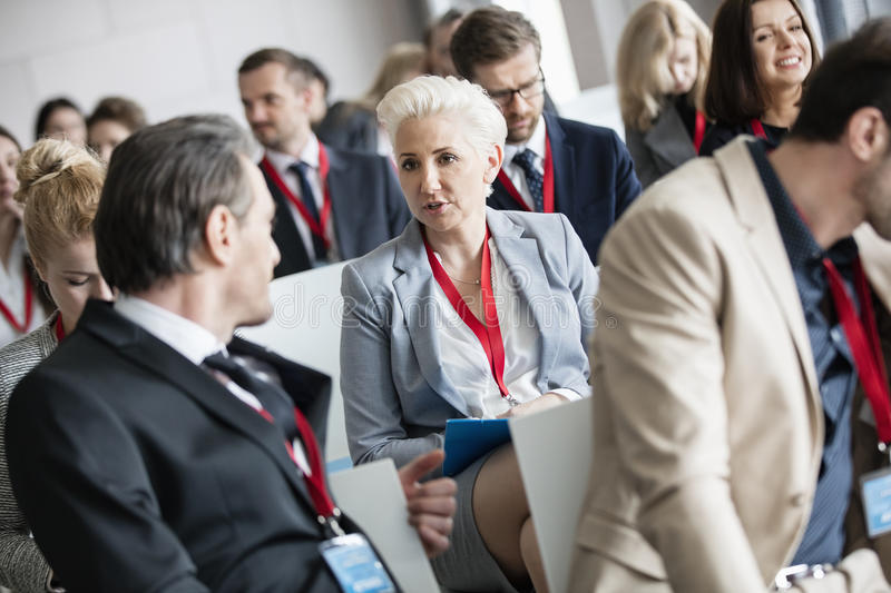 Businessman talking to businesswoman in seminar hall at convention center stock photos