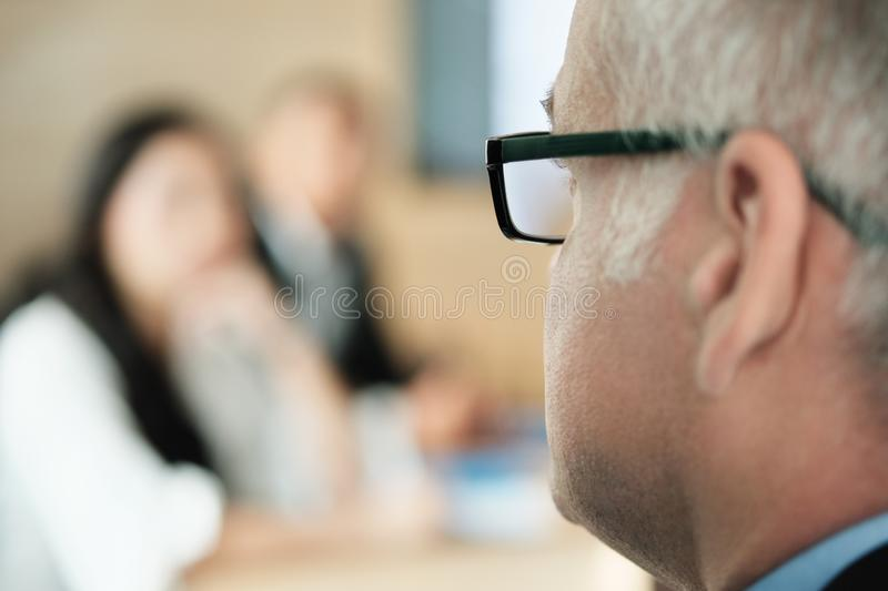 Businessman Talking To Colleagues and Clients In Office Meeting Room royalty free stock image