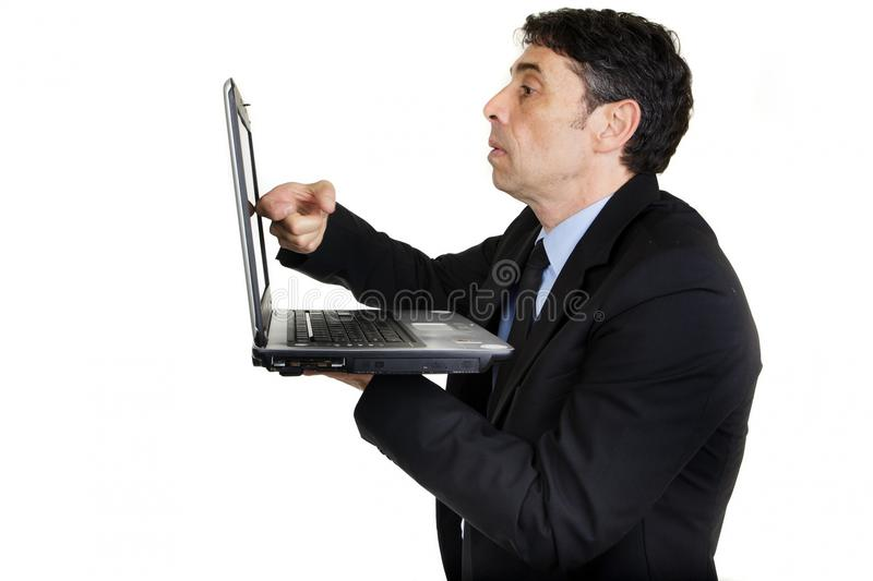 Businessman tapping his laptop. Side view of a serious businessman tapping his laptop screen with his finger as he stands holding it in his hand, upper body stock photography