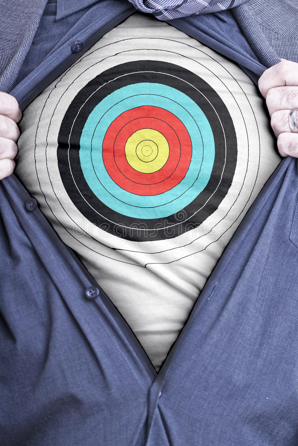 Businessman target. A businessman rips open his shirt and shows how perfect he is for your needs by showing off a target printed on a t-shirt stock photos