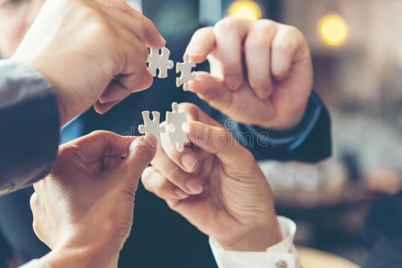 Businessman team work holding two jigsaw stock image