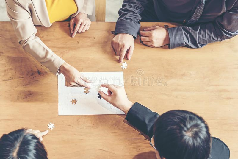 Businessman team work holding two jigsaw connecting couple puzzle piece for matching to goals target, royalty free stock photo