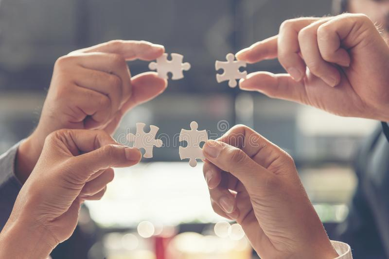 Businessman team work holding two jigsaw connecting couple puzzle piece for matching to goals target, royalty free stock image