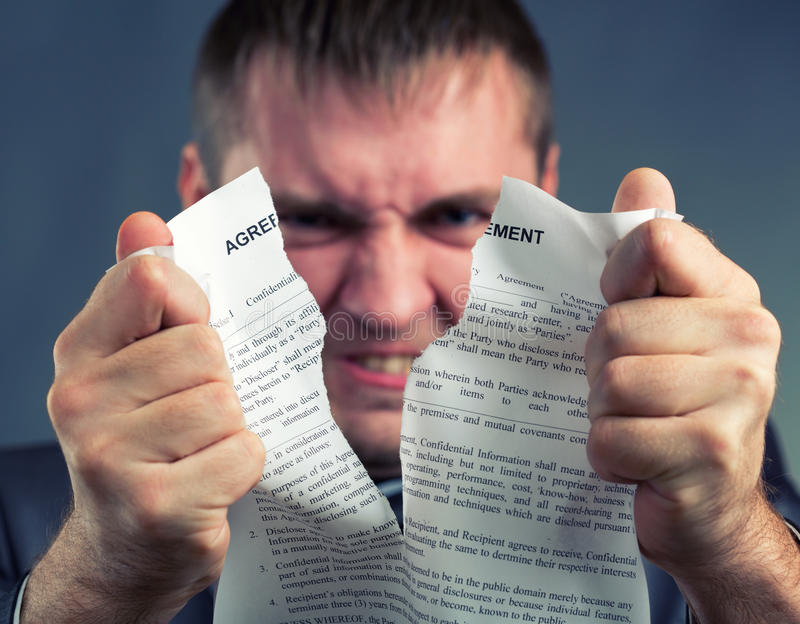 Businessman tearing agreement stock photography