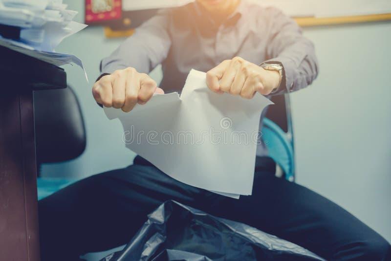 Businessman tearing blank paper apart stock photo