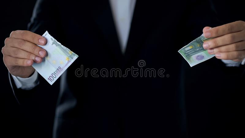 Businessman tearing euro bill out, currency devaluation, stock market crisis. Stock photo stock photography