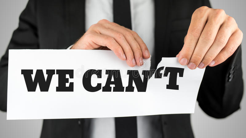 Businessman tearing up a sign saying - We Can't. Conceptual of successfully overcoming problems and challenges, positive attitude and providing the service royalty free stock images