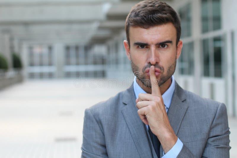 Businessman telling you to shut up.  stock image