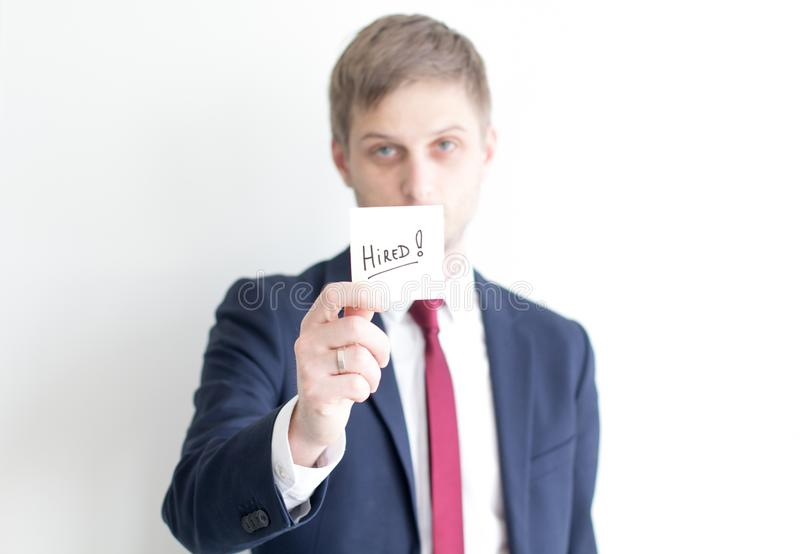 Businessman with text Hired. Young businessman showing the sticker with text: Hired royalty free stock photo