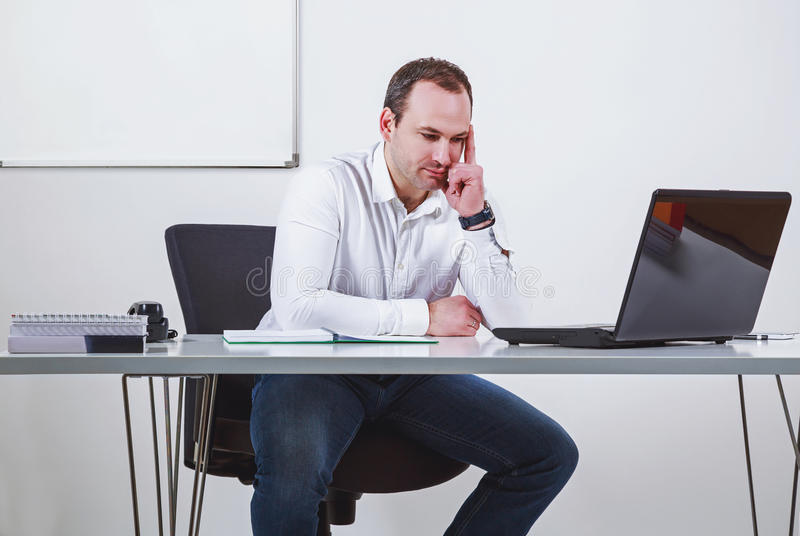 Businessman thinking in front of laptop royalty free stock images