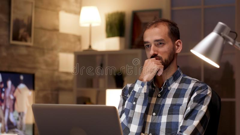 Businessman thinking and holding arms crossed while working on laptop royalty free stock photography
