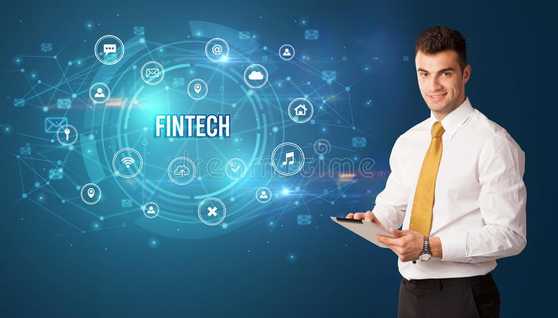 Businessman thinking about modern technology. Businessman thinking in front of technology related icons and FINTECH inscription, modern technology concept stock photos