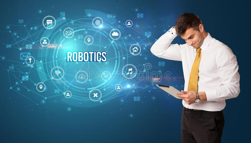 Businessman thinking about modern technology. Businessman thinking in front of technology related icons and ROBOTICS inscription, modern technology concept royalty free stock images
