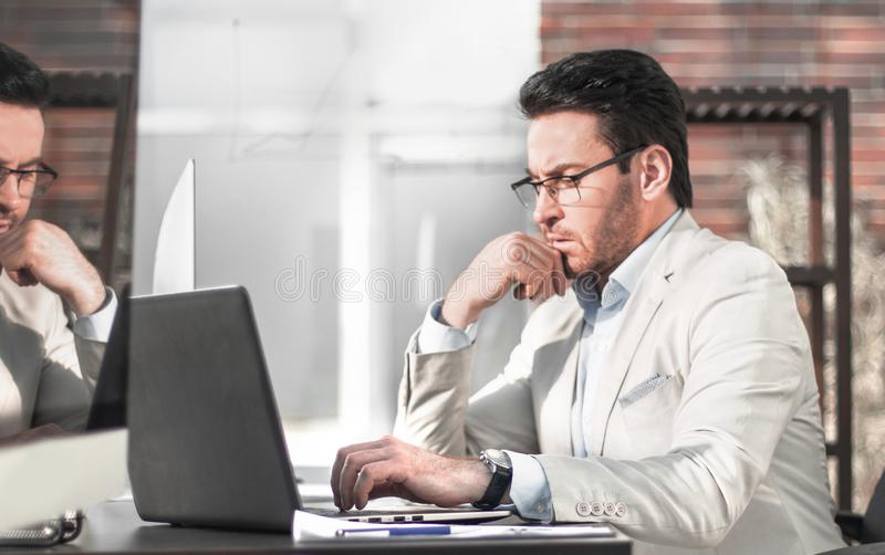 Businessman thinking in the office behind a glass wall. stock images