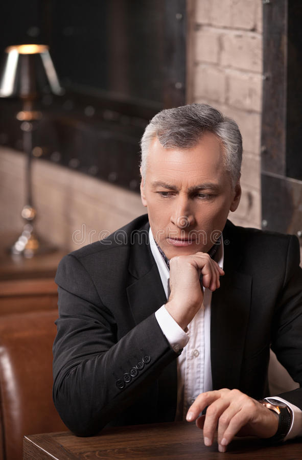 Businessman thinking about options. Thoughtful mature businessman sitting with his hand on chin and looking away stock image